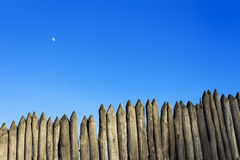 Palisade stockade palings logs and blue sky. Abstract background, old, ancient Royalty Free Stock Image