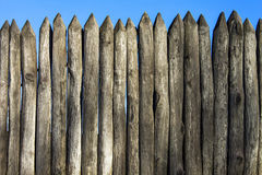 Palisade stockade palings logs and blue sky. Abstract background, old, ancient Royalty Free Stock Images