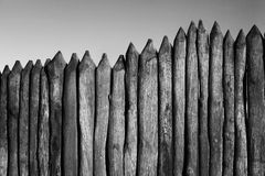 Palisade stockade palings logs and sky. Abstract background, old, ancient. Black and white image Stock Photo