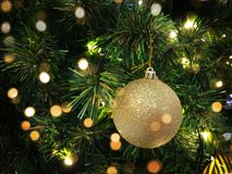 Palla alta vicina di natale che appende sull'albero con il concetto caldo del bokeh dorato immagine stock libera da diritti