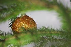 Palla ambrata sull'albero di Natale su un fondo bianco luccichii ambrati della pietra preziosa alla luce Luce arancio Decorazioni immagine stock libera da diritti