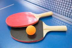 Palla arancio per ping-pong e due racchette del co rosso e nero Fotografie Stock Libere da Diritti