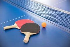 Palla arancio per ping-pong e due racchette del co rosso e nero Fotografia Stock