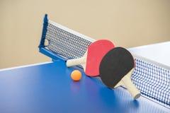 Palla arancio per ping-pong e due racchette del co rosso e nero Immagini Stock Libere da Diritti