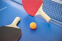 Palla arancio per ping-pong e due racchette del co rosso e nero Fotografia Stock Libera da Diritti