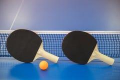 Palla arancio per ping-pong e due racchette del co rosso e nero Fotografie Stock