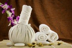 Palla, asciugamani ed orchidea di erbe della stazione termale sulla stuoia di bambù Immagini Stock