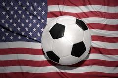 Palla in bianco e nero di calcio sulla bandiera nazionale degli Stati Uniti d'America immagine stock libera da diritti
