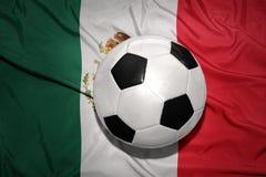 Palla in bianco e nero di calcio sulla bandiera nazionale del Messico Immagine Stock Libera da Diritti