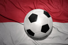 Palla in bianco e nero di calcio sulla bandiera nazionale dell'Indonesia immagini stock libere da diritti