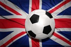 Palla in bianco e nero di calcio sulla bandiera nazionale della Gran Bretagna Immagine Stock