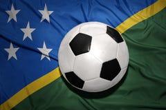 Palla in bianco e nero di calcio sulla bandiera nazionale di Solomon Islands Fotografia Stock Libera da Diritti