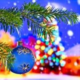 Palla blu di Natale davanti all'albero di Natale fotografie stock