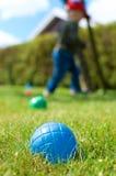 Palla blu di Petanque con il bambino che cammina nel fondo Fotografia Stock