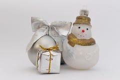 Palla d'argento di Natale con il pupazzo di neve e poco regalo su fondo bianco immagine stock