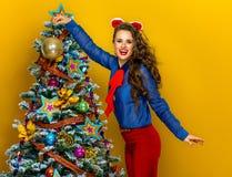 Palla d'attaccatura felice di Natale della donna elegante su un albero Immagini Stock