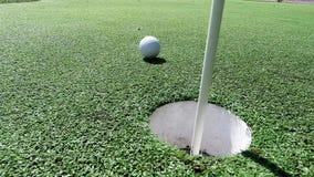Palla da golf bianca che colpisce il bastone della bandiera e che cade nel foro su verde mettente stock footage