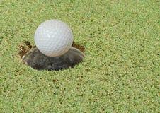 Palla da golf che cade per forare nel campo di corso fotografia stock