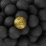 Palla da golf dorata con la palla nera Fotografia Stock