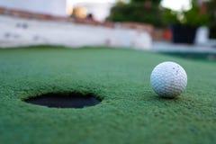 Palla da golf e foro in un campo del minigolf fotografia stock libera da diritti