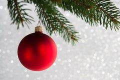 Palla decorativa rossa sull'albero di natale sul fondo del bokeh di scintillio Carta di Buon Natale Immagini Stock Libere da Diritti
