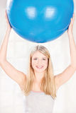 Palla dei pilates della tenuta della donna sopra la sua testa Immagini Stock