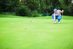 Palla della marcatura del giocatore di golf sul verde mettente Fotografia Stock
