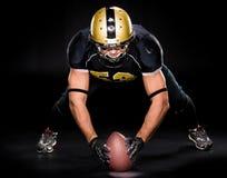 Palla della tenuta del giocatore di football americano fotografia stock libera da diritti