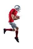 Palla della tenuta del giocatore di football americano mentre correndo fotografie stock