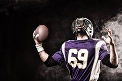 Palla della tenuta del giocatore di football americano in sue mani in fumo fondo nero, spazio della copia Il concetto dell'americ fotografia stock libera da diritti