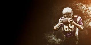 Palla della tenuta del giocatore di football americano in sue mani in fumo fondo nero, spazio della copia Il concetto dell'americ immagine stock