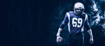 Palla della tenuta del giocatore di football americano in sue mani in fumo fondo nero, spazio della copia Il concetto dell'americ immagini stock