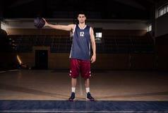 Palla della tenuta del giocatore di pallacanestro in una mano, corte Fotografia Stock