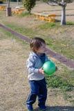 Palla della tenuta del ragazzo in campo da giuoco Fotografia Stock Libera da Diritti