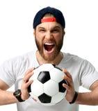 Palla della tenuta dell'uomo del fan di calcio che celebra grida gridanti di risata felici fuori alto in cappuccio isolato su bia Immagini Stock