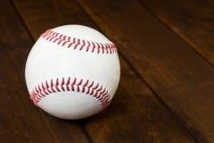 Palla di baseball sul bordo di legno Immagine Stock