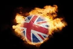 Palla di calcio con la bandiera della Gran Bretagna su fuoco Immagine Stock Libera da Diritti