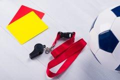 Palla di calcio, due carte di pena e un fischio per l'arbitro, su un fondo grigio Immagini Stock Libere da Diritti