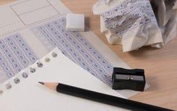 Palla di carta sgualcita del modulo di risposta classico d'annata con riduzione della matita, dell'affilatrice e della carta Immagine Stock