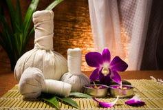 Palla di compressione di erbe della stazione termale con le candele e l'orchidea Fotografia Stock Libera da Diritti