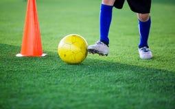 Palla di controllo del calciatore del bambino intorno al creatore del cono per addestramento di calcio immagine stock