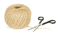 Palla di corda e delle forbici naturali su fondo bianco Immagine Stock