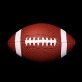 Palla di football americano sul nero fotografia stock libera da diritti