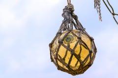 Palla di galleggiante di vetro gialla storica di pesca che appende in una rete alla d Fotografia Stock Libera da Diritti