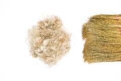 Palla di lana e di capelli marroni dell'animale domestico con la fine della scopa su lana marrone e scopa isolate su fondo bianco Immagini Stock