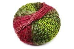 Palla di lana variopinta, rosso e verde su bianco Immagine Stock