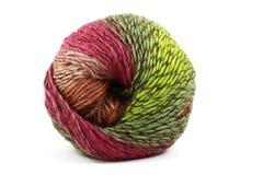 Palla di lana variopinta, rosso e verde su bianco Fotografie Stock