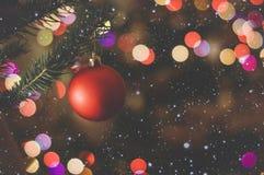 Palla di Natale su un ramo dell'abete sui precedenti di variopinto fotografia stock libera da diritti