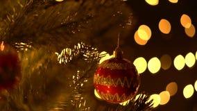 Palla di Natale sui rami dell'abete con il fondo delle luci del bokeh stock footage