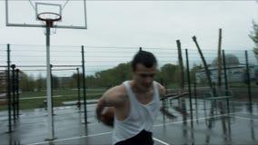 Palla di pallacanestro di stile libero sul campo da giuoco della via video d archivio